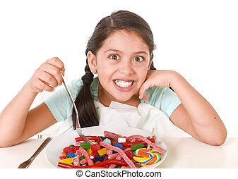 female child eating dish full of candy in sugar excess and sweet nutrition abuse