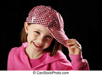 Young girl wearing a pink sequin baseball cap smiling, on black background