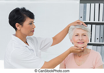 Female chiropractor doing neck adjustment in the medical...