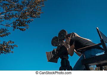 female cinema director looking at camera viewfinder