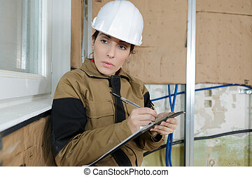 female civil engineer taking notes at construction site