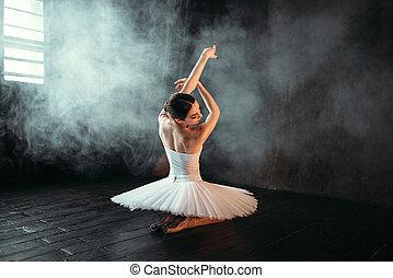 Female classical ballet performer sitting on floor
