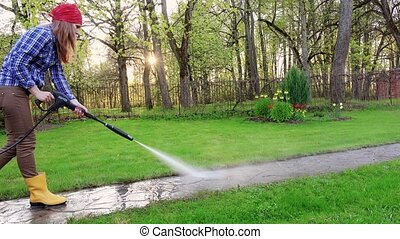 female cleaner working on pathway in garden. Seasonal summer...