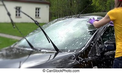 Female cleaning dirt from car with sponge and automobile...