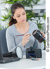 female cleaning dirty lens with a brush