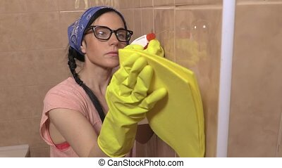 Female cleaning tiles in bathroom