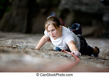 Female Climber - A female climber on a steep rock face ...