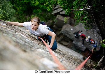 Female Climber - A female climber on a steep rock face. ...