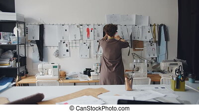 Female clothes designer looking at drawings of garments...