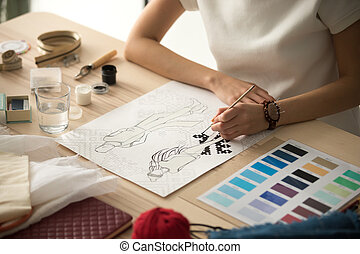 Female clothing designer coloring sketch with brush at workplace