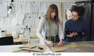 Female clothing designer is drawing outlines of new garment on fabric with chalk while her colleague is helping her and using tablet. Technologies in clothes manufacturing concept.
