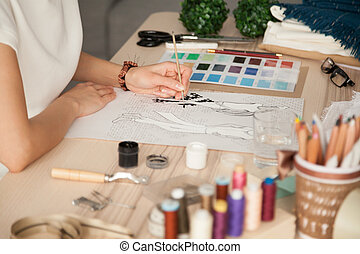 Female clothing designer sketching with brush at workplace