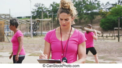 Front view close up of a Caucasian female coach standing at boot camp, writing on a clipboard and looking up to camera, with multi-ethnic group of female friends exercising in the background, all wearing pink t shirts, in slow motion