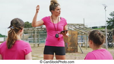 Front view close up of a Caucasian female coach standing at boot camp holding a tablet computer and giving instructions to a multi-ethnic group of female friends, all wearing pink t shirts, in slow motion