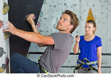 female coach timing the wall climber