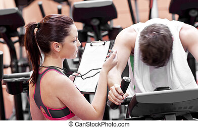Female coach using a chronometer while man is pedaling on a bicycle in a fitness centre