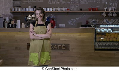 Female coffee shop owner standing in front of the counter...