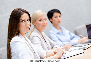 Female colleagues discuss business plan sitting at the meeting hall. Leadership team