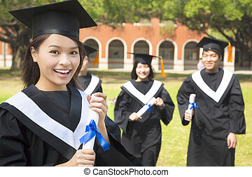 female college graduate with classmates and holding a diploma