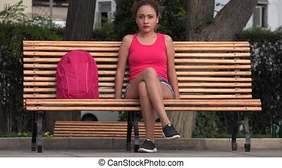 Female College Student Sitting On Park Bench