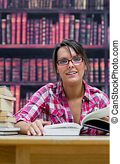 Female college student sitting with books at library