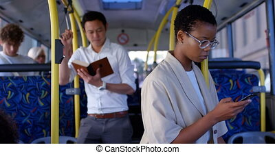 Female commuter using mobile phone while travelling in bus ...