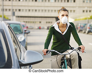 female commuter - woman with dust mask commuting on bicycle
