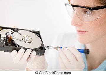 Female computer engineer - woman repair hard disc - Female...