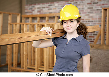 A young female apprentice working on a construction site.