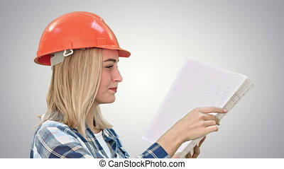 Female construction engineer reading plans and talk to workers on white background.