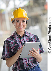 female construction engineer working on laptop at site