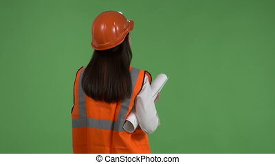Female construction manager against green screen. Rear view of woman in orange safety vest and helmet holding blueprint