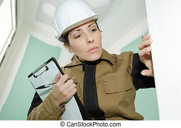 female construction worker checking the finished of a wall