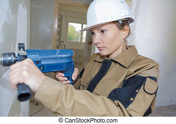 female construction worker demolishing old brick wall with drill