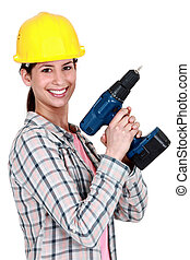 Female construction worker holding a drill