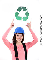 Female construction worker holding a recycle sign