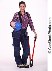 Female construction worker holding a large tool