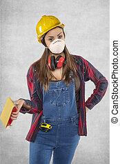 Female construction worker holding sandpaper