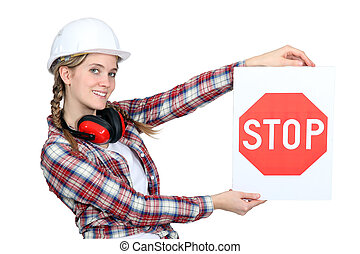 Female construction worker holding stop sign