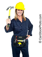 Female construction worker holding up hammer