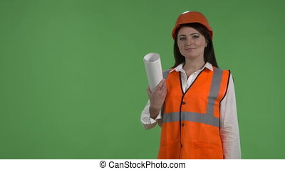 Female construction worker on building site against green screen