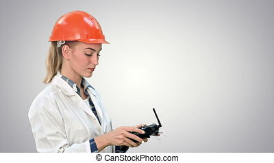Female construction worker operating a crane using remote control on white background.