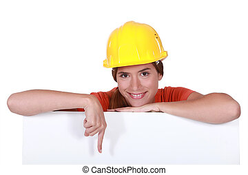 Female construction worker pointing to blank poster