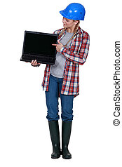 Female construction worker pointing to laptop