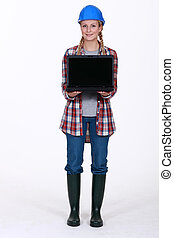 Female construction worker presenting laptop