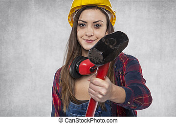 Female construction worker shows a big hammer