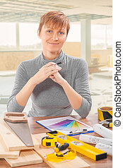 female construction worker sitting at table with tools