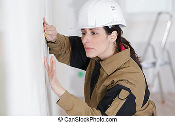 female construction worker smoothing wall surface
