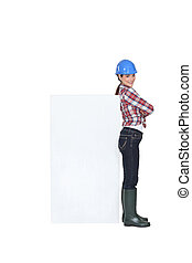 Female construction worker with a board left blank for your...