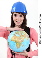 Female construction worker with a globe